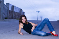 Woman lay down. Woman poses lay down in the road at night royalty free stock image