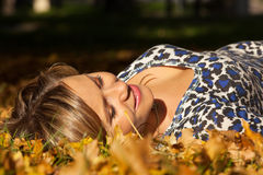 Woman lay on ground in leaves Stock Images