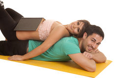 Woman lay on mans back book on her stomach Stock Photo