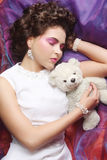Woman lay on organza with teddy bear Royalty Free Stock Images