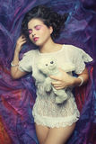 Woman lay on organza with teddy bear Royalty Free Stock Photos