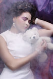Woman lay on organza with teddy bear Stock Images