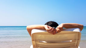 Woman lay on the white armchair on the beach Stock Photography