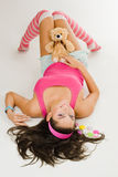 Woman lay on white floor in pink clhothes with toy Royalty Free Stock Photo