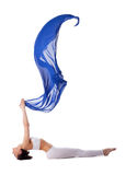Woman lay in yoga pose with blue flying fabric Stock Photography