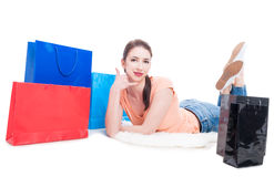 Woman laying around shopping bags making calling gesture Stock Photography