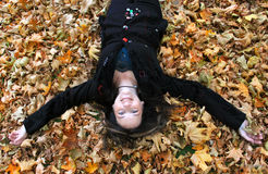 Woman laying in autumn leaves. Beautiful woman in her forties is happily laying on the ground covered by a bed of autumn leaves Stock Photography