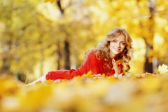 Woman laying on autumn leaves. Happy young woman laying on autumn leaves in park stock images