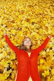 Woman laying on autumn leaves. Happy young woman laying on autumn leaves in park royalty free stock photos