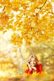 Woman laying on autumn leaves. Happy young woman laying on autumn leaves in park stock photos