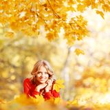 Woman laying on autumn leaves. Happy young woman laying on autumn leaves in park royalty free stock images
