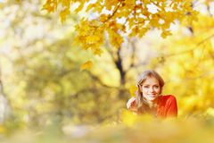 Woman laying on autumn leaves. Happy young woman laying on autumn leaves in park stock photography
