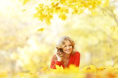 Woman laying on autumn leaves Royalty Free Stock Images