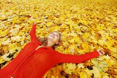 Woman laying on autumn leaves. Happy young woman laying on autumn leaves in park royalty free stock photography