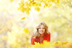 Woman laying on autumn leaves. Happy young woman laying on autumn leaves in park stock image