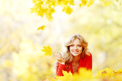 Woman laying on autumn leaves Stock Photos