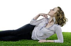 Woman laying back on grass as she looks to the sky Royalty Free Stock Photos