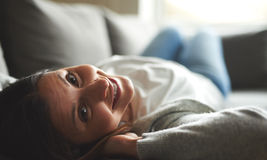 Woman laying on back with head tilted back smiling. Stock Image