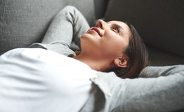 Woman laying on back resting on couch. Royalty Free Stock Photos