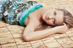 Woman laying on bamboo mat Royalty Free Stock Photo