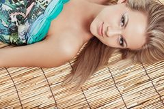 Woman laying on bamboo mat Royalty Free Stock Image