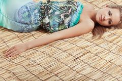 Woman laying on bamboo mat Stock Photography