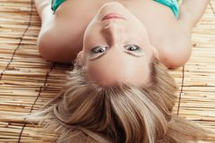 Woman laying on bamboo mat Royalty Free Stock Photography