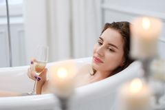 Woman laying in a bath with glass of champagne.  stock photos