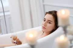 Woman laying in a bath with glass of champagne.  royalty free stock photography
