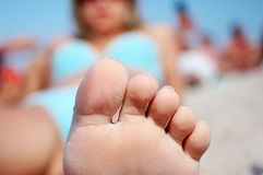 Woman laying on the beach with foot and toes Royalty Free Stock Images