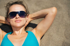 Woman laying on beach sand Stock Photography