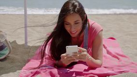 Woman laying on beach using cell phone. Cute grinning woman in long brown hair laying on pink blanket at sunny ocean beach using cell phone stock video
