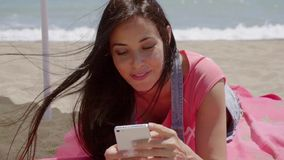 Woman laying on beach using cell phone. Cute grinning woman in long brown hair laying on pink blanket at sunny ocean beach using cell phone stock video footage