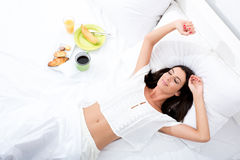 Woman laying in the bed with breakfast Royalty Free Stock Photo