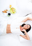 Woman laying in the bed with breakfast Stock Photos