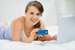 Woman laying on bed with credit card and laptop Stock Images