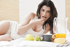Woman laying on bed and having breakfast Royalty Free Stock Photography