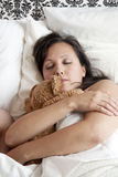 Woman laying in bed hugging a teddy bear Royalty Free Stock Images