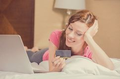 Woman laying in bed with laptop holding credit card shopping online Royalty Free Stock Photography