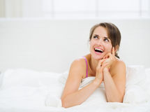 Woman laying in bed and looking on copy space Royalty Free Stock Photography