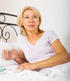 Woman laying in bed with pills Royalty Free Stock Images