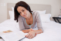 Woman laying on the bed reading a magazine Royalty Free Stock Photos