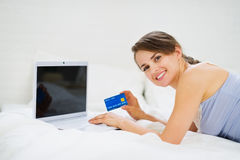 Woman laying on bed and shopping on net Royalty Free Stock Photos
