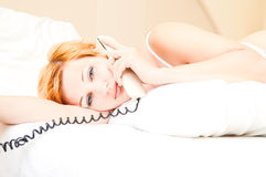 Woman laying on bed talking on cordless telephone Royalty Free Stock Image