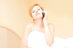 Woman laying on bed talking on cordless telephone Stock Photography