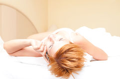Woman laying on bed talking on cordless telephone Royalty Free Stock Photo