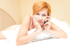 Woman laying on bed talking on cordless telephone Stock Photo