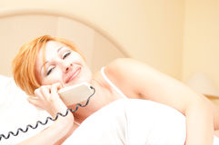 Woman laying on bed talking on cordless telephone Stock Photos