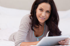 Woman laying in the bedroom with tablet Royalty Free Stock Photography
