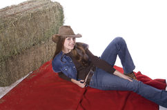 Woman laying on blanket by hay Stock Photo